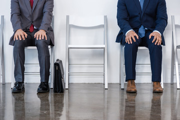 businessmen in suits sitting on chairs at white waiting room. business meeting