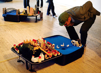 A MAN LOOKS AT A MODEL OF THE CITY OF HONG KONG INSIDE A SUITCASE DURING BIENNALE EXHIBITION IN SYDNEY.
