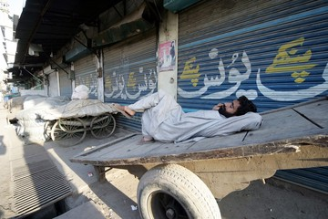 A Pakistani labourer rests on his push cart in the Pakistani city of Rawalpindi.
