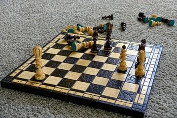 Шахматная доска с шахматами на сером шерстяном ковре