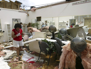 Woman walks through destroyed shop after Hurricane Frances tore off roof.