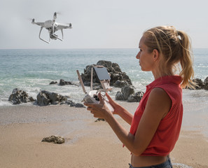 Pretty woman standing on the beach with remote controller of drone over sea and sky background