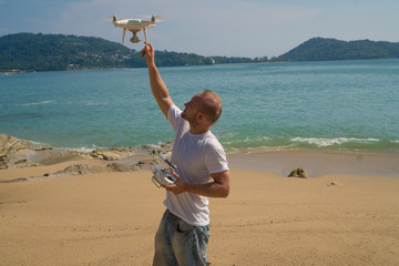 Man catching drone while standing on the beach with remote controller of drone in sunny summer day over sea and sky background