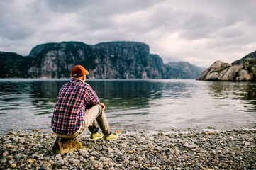Lonely traveler tourist man resting on shore of fjord in Norway with  far view of water and mountains valley at horizon in summer cloudy day. Contemplation. Reflection. Holidays. Vacation. Nature. Wall mural