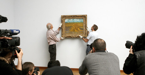 Media take pictures as employees Bosch and Marti fix the painting 'Wheatfield with Sheaves' of late Dutch artist van Gogh out at a wall at the Kunstmuseum Basel in Basel