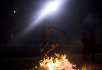 A boy jumps over a bonfire during the traditional San Juan's (Saint John) night in Malaga