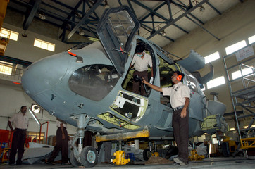 Employees of Hindustan Aeronautics Ltd. work inside a helicopter workshop in Bangalore