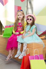two Cheerful  little girls walking with shopping bags. two pretty girls in dresses and sunglasses near shopping mall having fun.