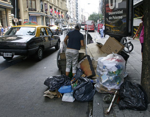 A woman looks for recyclables items to be sold in downtown Buenos Aires