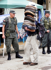 Colombian man sells hats next to policemen on streets of Viota in Colombia