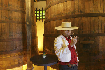 A man smells a glass of wine in a winery in Santiago