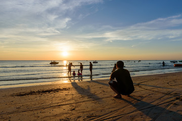 Chao Lao Beach at Chanthaburi  Dec 18,2016 : Men taking picture  women and children playing in the sea, Chanthaburi Province inTHAILAND