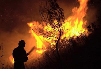 A FIREMAN DIRECTS WATER TOWARDS FLAMES NEAR SAINTE BAUME.