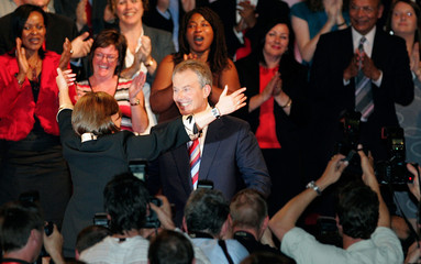 Britain's PM Blair is hugged by his wife Cherie following his keynote speech on the third day of the Labour Party's annual conference in Manchester