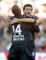 Lyon's Frau and Govou celebrate their team scoring against Nantes during French Ligue 1 soccer match ...
