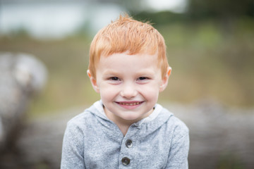 Boy with red hair smiling towards camera, portrait