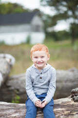 Portrait of boy sitting on log smiling towards camera