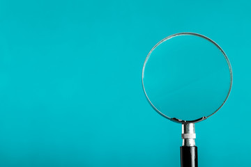 Magnifying glass on blue color background.