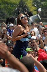 A woman dodges a flying beer can after baring her breasts during the massive infield party before the Preakness Stakes in Baltimore