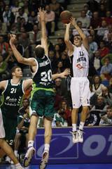 Partizan Belgrade's Uros Tripkovic goes to the basket as Unicaja's Carlos Jimenez and Robert Archibald try to block him in Malaga