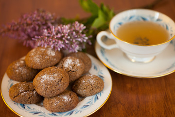 a plate of Molasses cookies with green tea in a vintage porcelain teacup with purple flowers