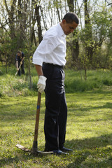 U.S. President Barack Obama is pictured with a gardening tool as he rests during a tree planting at Kenilworth Aquatic Gardens in Washington