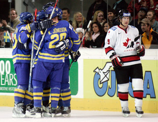 Canada's Shane Doan skates past Sweden players celebrating another second period goal at IIHF World ...