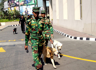 Bangladeshi troopers with sniffer dogs walk outside the entrance of Dhaka's Sheraton Hotel.