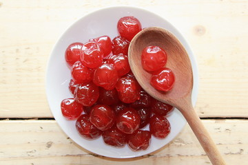 Red cherries on a White plate with a wooden spoon