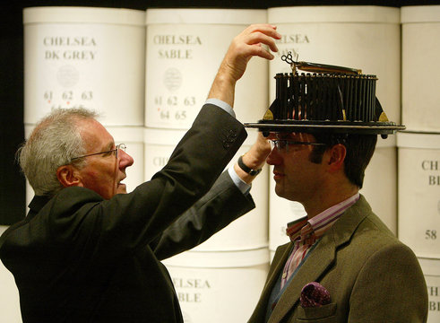 To accompany feature Life Climber - Sales consultant measures customer for hat size at Lock & Co ...