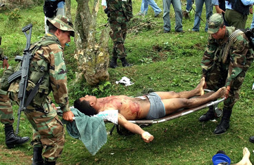 COLOMBIAN SOLDIERS CARRY BODY OF PARAMILITARY FIGHTER.