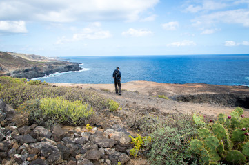 One person standing in beautiful landscape with cliffs and sea in Gran Canaria, Canary Islands - Stock Photo