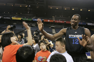 Dwight Howard of Orlando Magic greets a girl during a basketball session at the Special Olympics basketball clinic in Macau