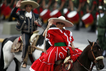 """A woman, dressed as a """"Charro"""", rides a horse during a military parade celebrating Independence Day in Mexico City"""