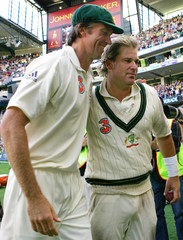 Australia's Warne and McGrath walk off the ground after they won the fourth Ashes cricket test against England at the Melbourne Cricket Ground