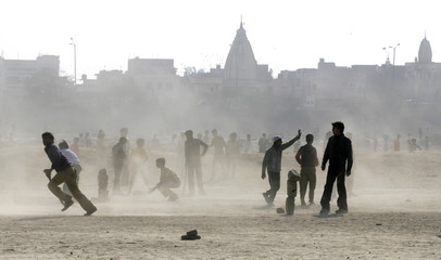 Boys play cricket during a dust storm at a ground in New Delhi