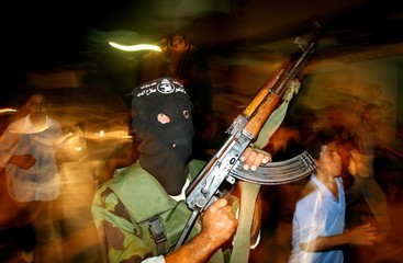 A Palestinian member of Popular Resistance Committees carries his gun as he marches during the group ...