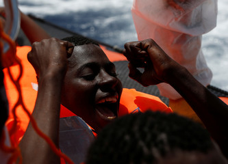A migrant reacts after being rescued by the Malta-based NGO Migrant Offshore Aid Station ship Phoenix during a rescue operation in the central Mediterranean off the Libyan coastal town of Sabratha
