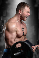 Brutal strong athletic men pumping up muscles train in gym
