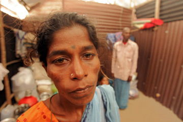 Lakshmi Kolandavelu (L) stands inside a small cubicle made of thick cardboard walls and tin sheet roofs.