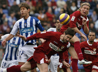 Sevilla's Christian Poulsen goes for a header during their Spanish first division match in Huelva
