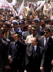 Algerian President Abdelaziz Bouteflika (C Front) waves to the crowd as he walks with officials and ..