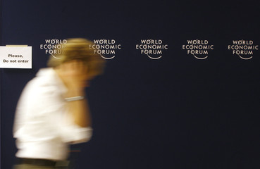 A journalist makes a phone call as he walks past the official logo of the World Economic Forum in Davos