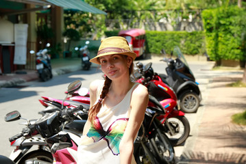 Pretty girl in hat. Smiling on motorbikes background. Thailand.