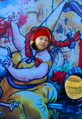 A Chinese girl takes pictures behind a cartoon model in a park during the Chinese Lunar New Year in ..