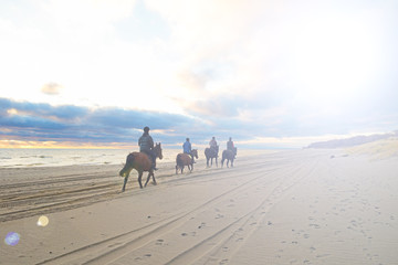 People on horses near the ocean and the sun in the sky shines in cloudy weather.