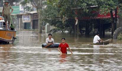 A girl wades along a flooded road  in Thach Thanh district