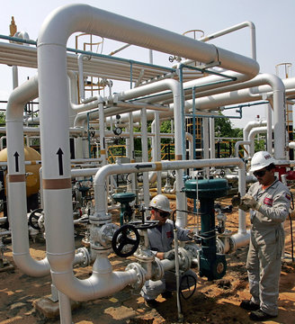 An oil worker conducts routine maintenance on a gas plant at field Boscan, operated under a joint ve..