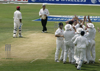 ENGLANDS HARMISON MOBBED BY TEAMMATES AFTER ONE HIS SEVEN WICKETS IN WIN AGAINST WEST INDIES.