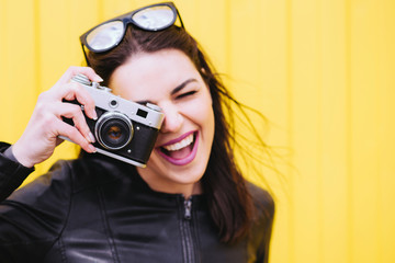 Attractive girl takes pictures with an old camera